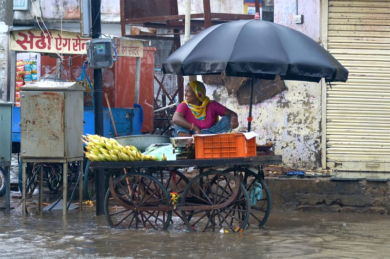 A lady sells rosted corn cops on a rainy day, in Ajmer, on July 18, 2018.