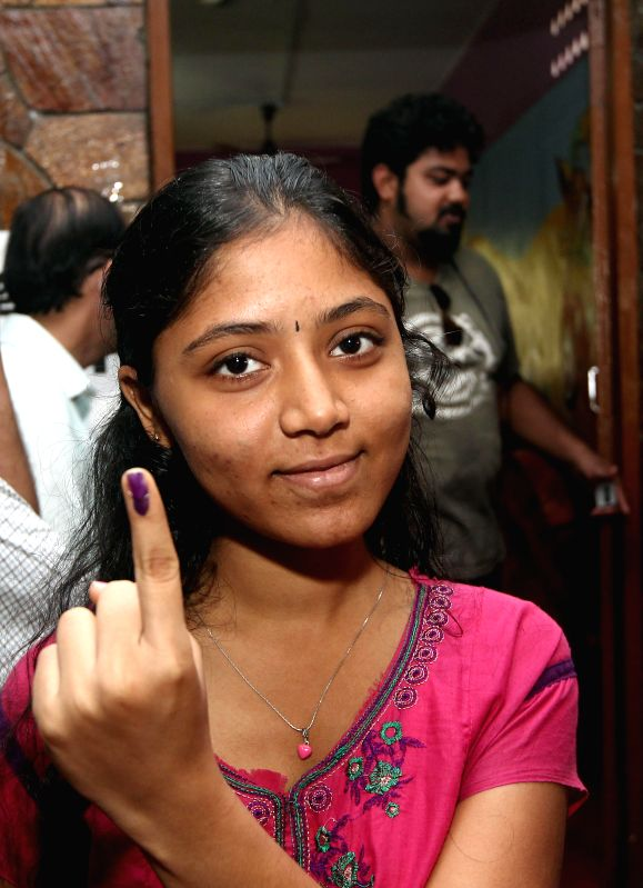 A lady shows her fore finger marked with phosphorous ink after casting her vote at a polling booth during the sixth phase of 2014 Lok Sabha Polls in Chennai on April 24, 2014.