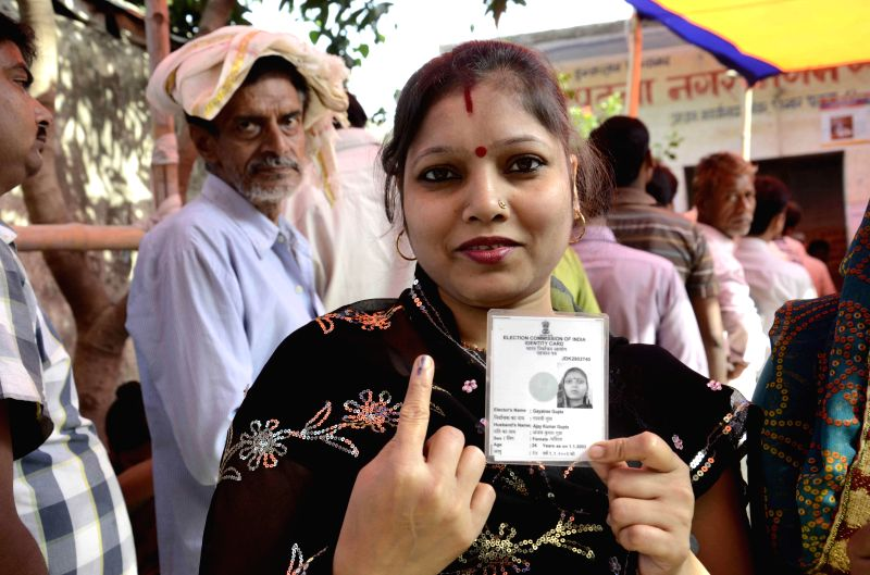 A lady shows her voters' identity card at a polling booth after casting her vote at polling booth during the fifth phase of 2014 Lok Sabha Polls in Patna on April 17, 2014. Elections are being held ..