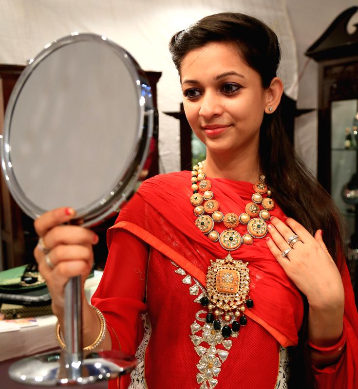 A lady tries out jewellery at Day- 1 of four-day long 8th Jewellers Association Show at Birla Auditorium in Jaipur on Aug 22, 2014.