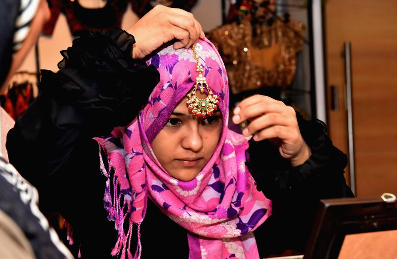 A lady tries out ornaments at a jewellery exhibition in Chennai on Aug 26, 2014.