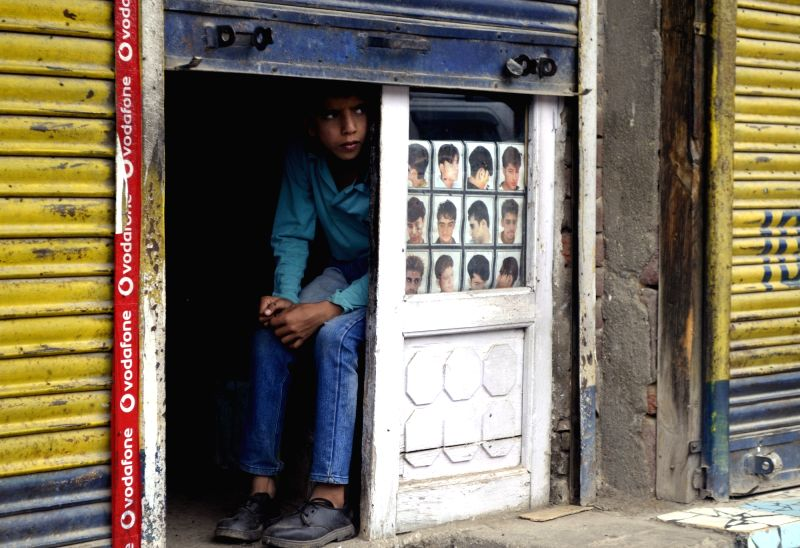 A little boy looks out of a shop window as a complete shutdown was observed in Baramulla town of Kashmir on July 18, 2016.
