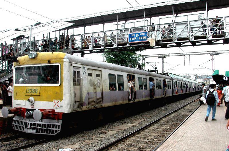 A local train arrives at platform of Dum Dum Station in Kolkata on July 8, 2014.