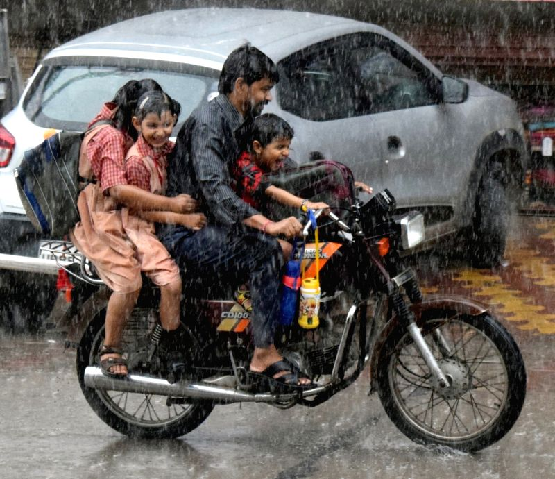 A man along with his children rushing home on a motorbike during heavy rains, in Mathura, on July 19, 2018.