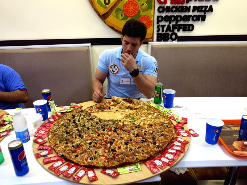 """A man attends a contest to eat pizza in Baghdad, Iraq, Oct. 31, 2015. A contest to eat larger pieces of Pizza named """"Away from violence"""" was held in one of ..."""
