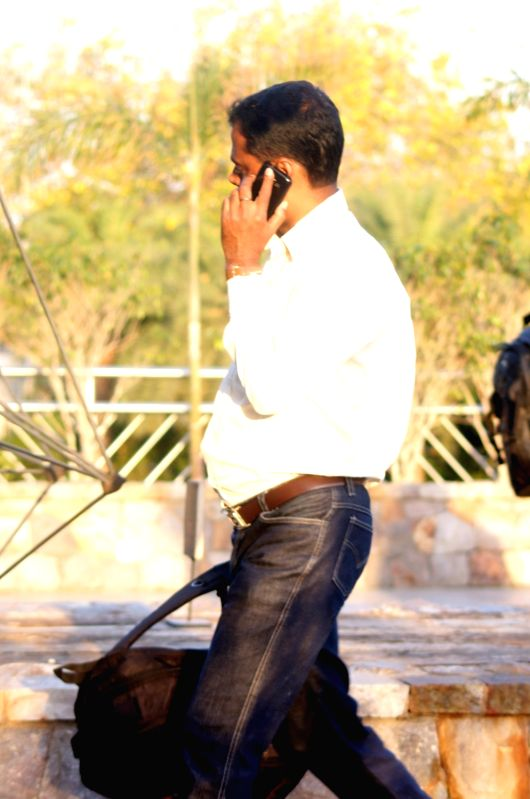 A man busy talking over his mobile phone. (File Photo: IANS)
