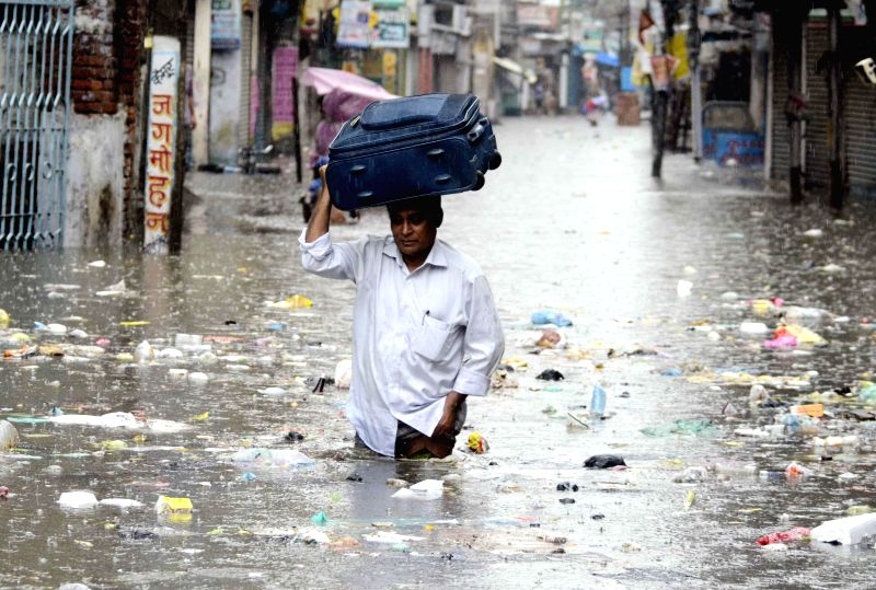A man carries his luggage on his head as he wades through a waterlogged street of Patna on Aug 14, 2014.