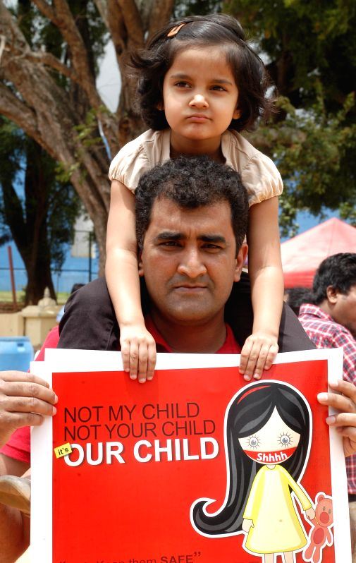 A man carrying his daughter on his shoulders  participates in a demonstration against  crime against women in Bangalore on July 20, 2014.