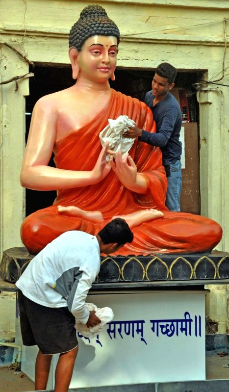 A man cleans a Buddha statue ahead of Buddha Purnima in Mumbai, on May 20, 2016.