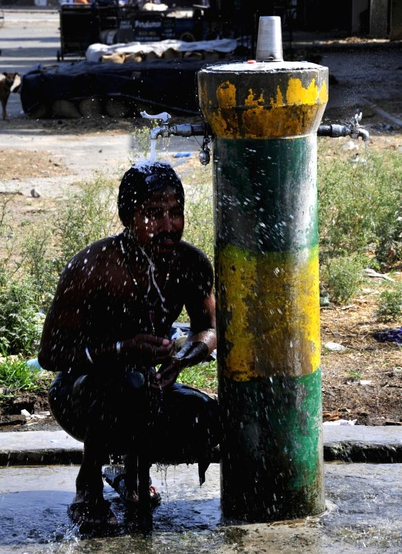 A man cools himself under a hand pump on a hot day in Amritsar, on June 4, 2017.