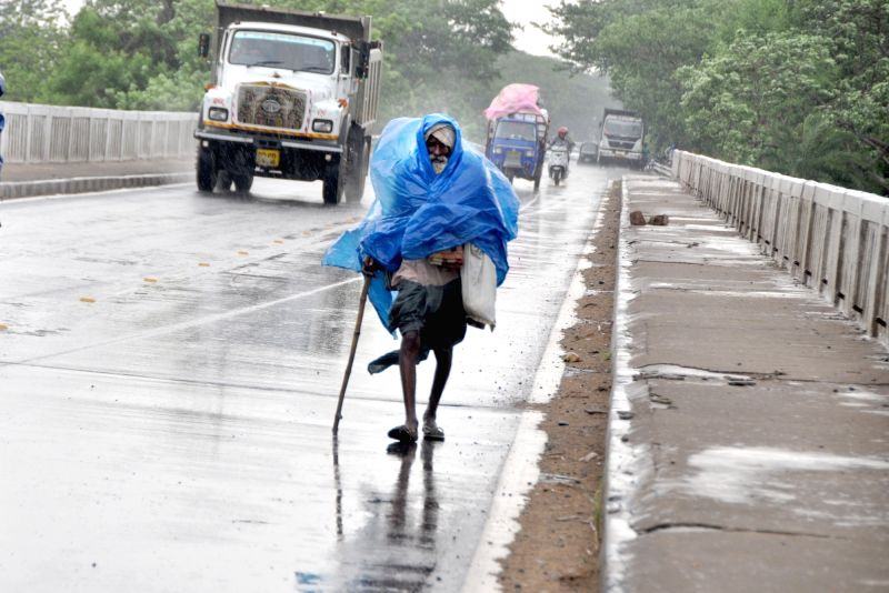 A man covers himself with a tarpaulin sheet during heavy rain in Bhubaneswar on June 1, 2016.