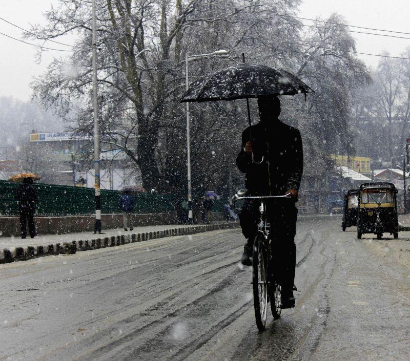 A man cycles on Srinagar roads during snowfalls on March 16, 2015.