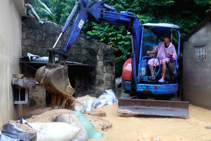 A man drives a forklift to clean the sludge in the front of a house in Ha Long city, Quang Ninh province, northeastern Vietnam, July 28, 2015. Floods and landslides ...
