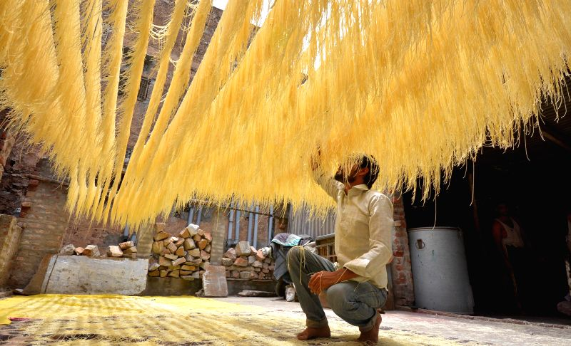 A man hangs strands of vermicelli to dry in sun at his house during the holy month of Ramadan in Jaipur on July 25, 2014.