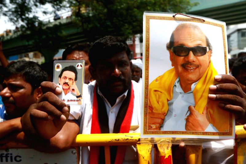 A man holding a portrait of  DMK President M. Karunanidhi and DMK working president M.K. Stalin outside the Kauvery Hospital where Karunanidhi is admitted, in Chennai, on July 30, 2018.
