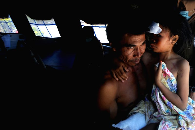 A man holds his daughter at a temporary tent at a hospital in North Lombok, West Nusa Tenggara, Indonesia, on Aug. 7, 2018. Death toll from Sunday's ...