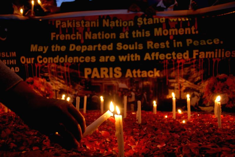 A man lights candles for the victims of the Paris terror attacks during a mourning ceremony in Islamabad, Pakistan, on Nov. 16, 2015.