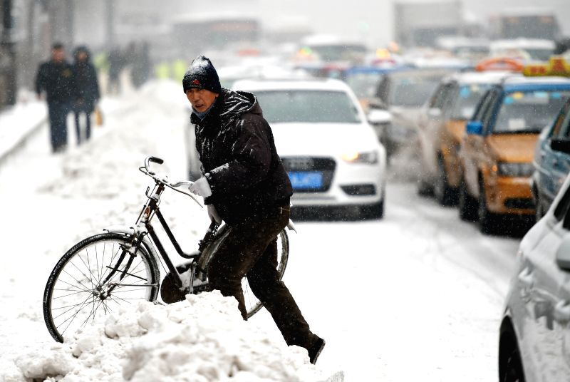A man moves a bike on Zhongshan Road in Harbin, capital of northeast China's Heilongjiang Province, Dec. 2, 2015. Heavy snowfall hit Heilongjiang on Wednesday. ...