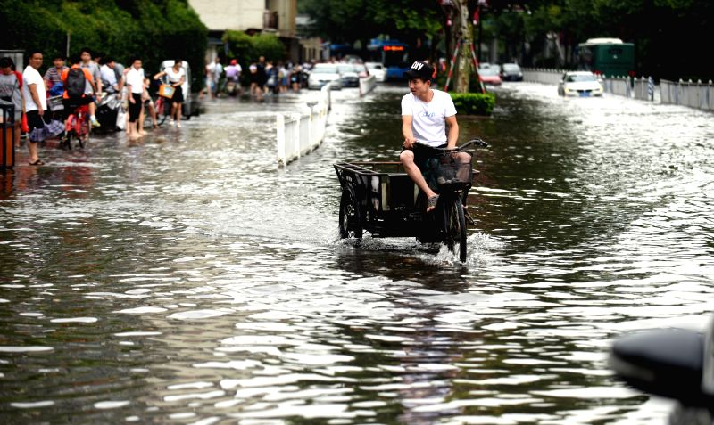 A man rides through flooded street in downtown Hangzhou, capital of east China's Zhejiang Province, July 21, 2015. A torrential rainfall hit the city Tuesday ...