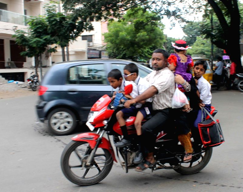 A man  rides with six persons including 4 children on his bike in Hyderabad on Aug 12, 2014.