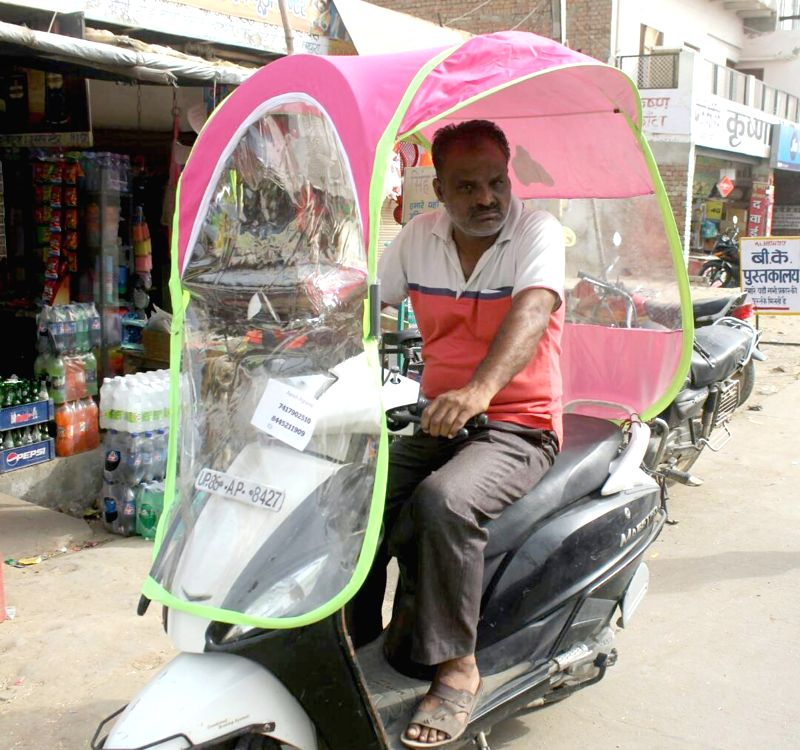 A man riding a two-wheeler fitted with an umbrella to beat the scorching heat in Mathura on April 22, 2017.