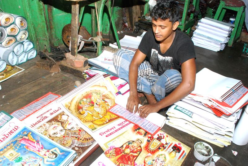 A man rolls Bengali calendars ahead of Bengali New year in Kolkata, on April 13, 2015.
