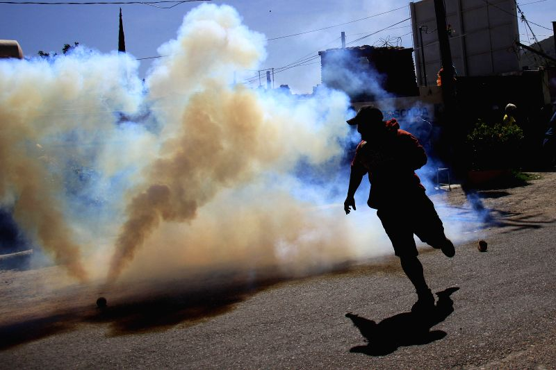 A man runs from tear gas during a clash between members of the section 22 of the National Coordinator of Education Workers (CNTE, for its acronym in Spanish) and ...