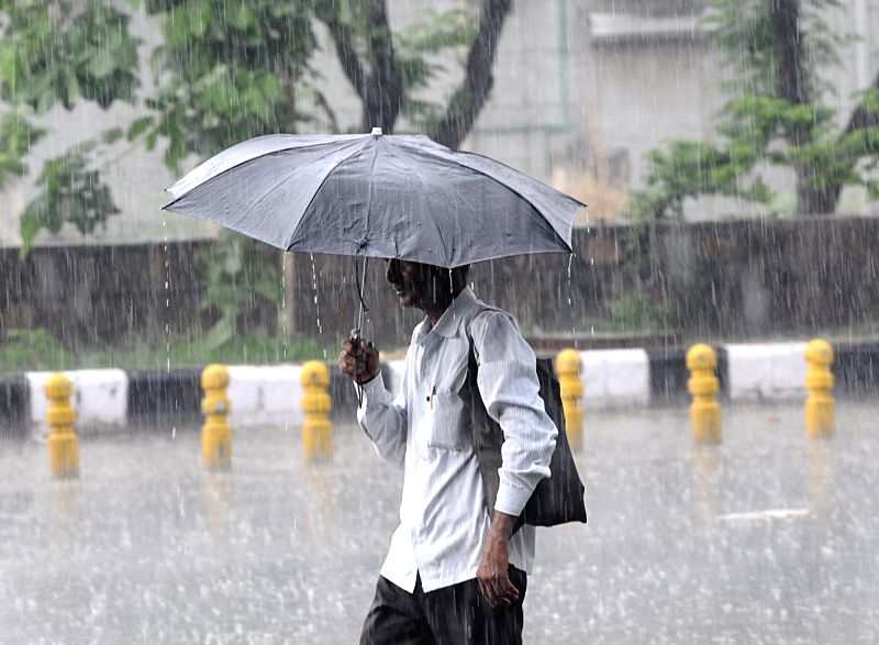 A man shields himself with an umbrella as heavy rains lash Delhi, on July 22, 2018.