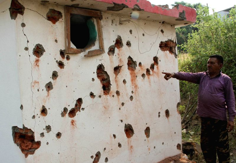 A man shows bullet ridden walls in Jhanghar village of Jammu and Kashmir's Nowshera sector of the LoC on May 15, 2017.