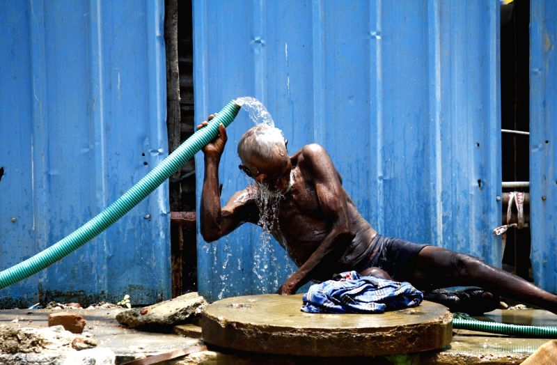 A man takes a bath in open on a hot day in Chennai on May 3, 2017.