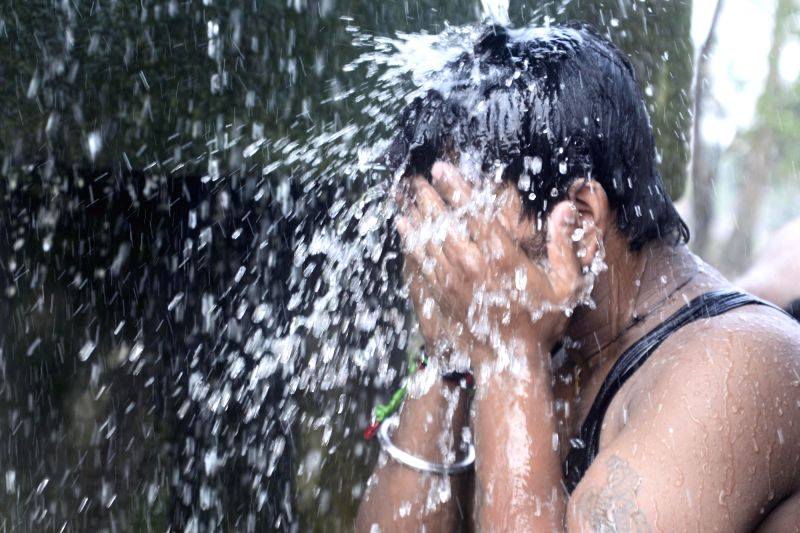 A man takes shower in open to beat the heat on a hot day in Kolkata on May 21, 2017.