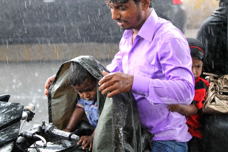 A man tries to protect a child sitting on his bike from rains in Hyderabad on Aug 8, 2014.