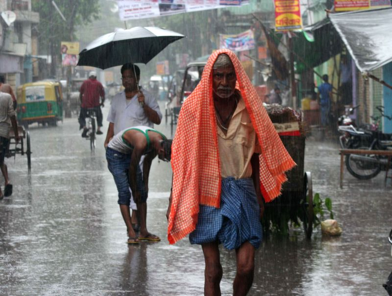 A man uses a towel to protect himself from the downpour in Varanasi on July 17, 2014.