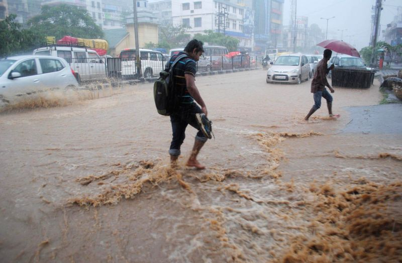 A man wades through water-logged streets of Guwahati during rains on Aug 20, 2014.