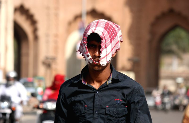 A man walks with his head covered on a hot day in Lucknow on April 22, 2015.