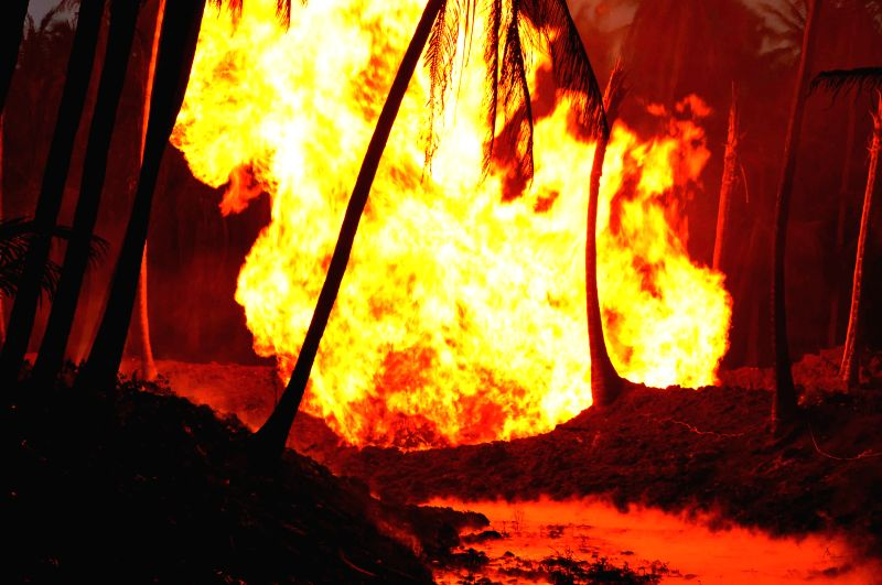 (A mobile camera photo) Flames rise after a blast in a gas pipeline belonging to GAIL in Nagaram village of Andhra Pradesh's East Godavari district on June 27, 2014.