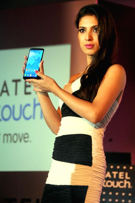 A model displays Alcatel One Touch's newly launched phone in Bangalore on Aug 21, 2014.