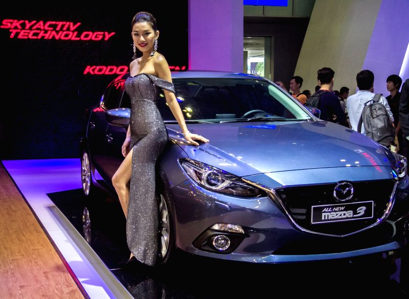 A model presents a All-new Mazda 3 during the Vietnam Motor Show 2015 at Saigon Exhibition and Convention Centre in Ho Chi Minh city, Vietnam, Oct. 28, ...