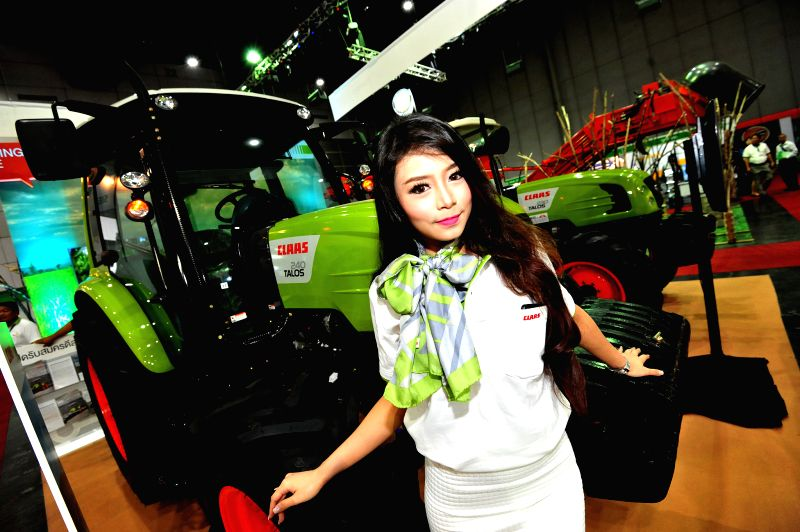 A model presents tractors during the World Sugar Expo 2015 in Bangkok, Thailand, Oct. 28, 2015. World Sugar Expo 2015, one of the world's largest specialized sugar ...