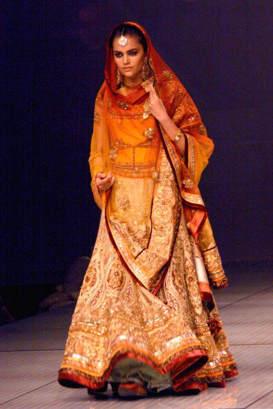 A model showcases fashion designer Tarun Tahiliani's creations during  `BMW India Bridal Fashion Week 2014` in New Delhi on Aug 7, 2014.