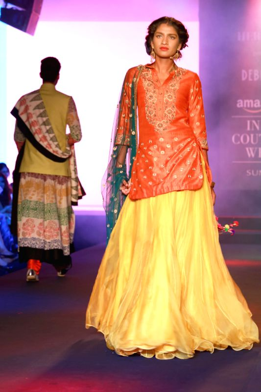 A model walks on the ramp displaying an outfit by designer Debarun Mukherjee during the Amazon India Couture Week 2015, in New Delhi on Aug 01, 2015.