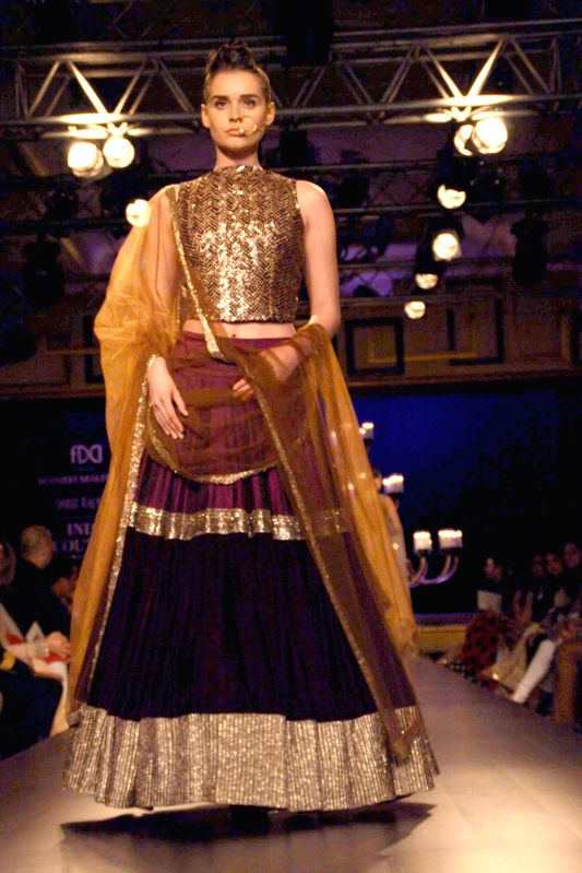 A model walks on the ramp for designer Manish Malhotra`s show during the India Couture Week 2014, in New Delhi on July 19, 2014.