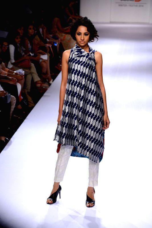 A model walks on the ramp for designer Sania Maskatiya during the Lakme Fashion Week (LFW) Winter/ Festive 2014 in Mumbai, on Aug. 20, 2014.