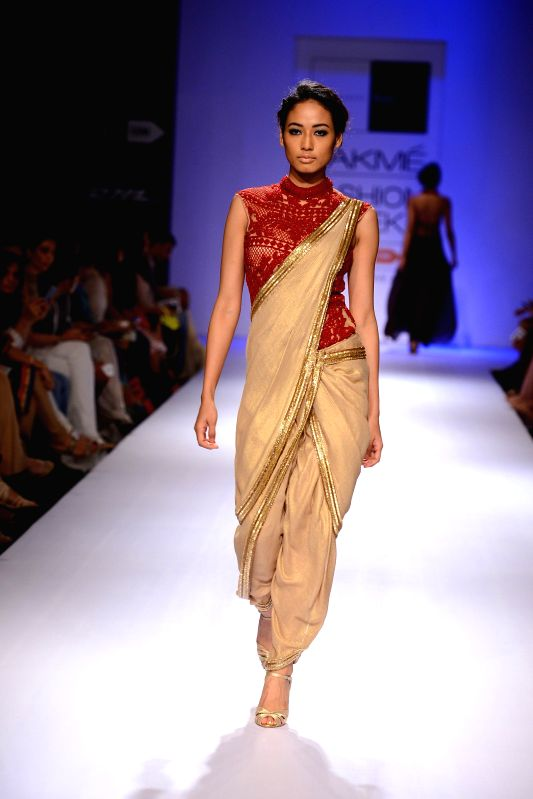 A model walks on the ramp for designer Sonakshi Raaj during Lakme Fashion Week (LFW) Winter/ Festive 2014, in Mumbai, on Aug. 24, 2014.