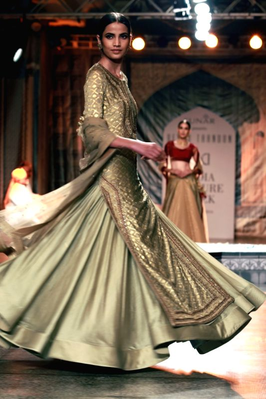 A model walks the ramp displaying an outfit by fashion designer Reynu Taandon during the India Couture Week 2016, in New Delhi on July 22, 2016.