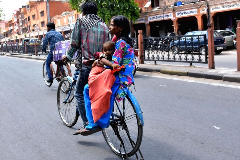 A mother holds her child as she rides pillion on a bicycle in Jaipur, on May 8, 2016. 8th May is observed as Mother's Day across the world.