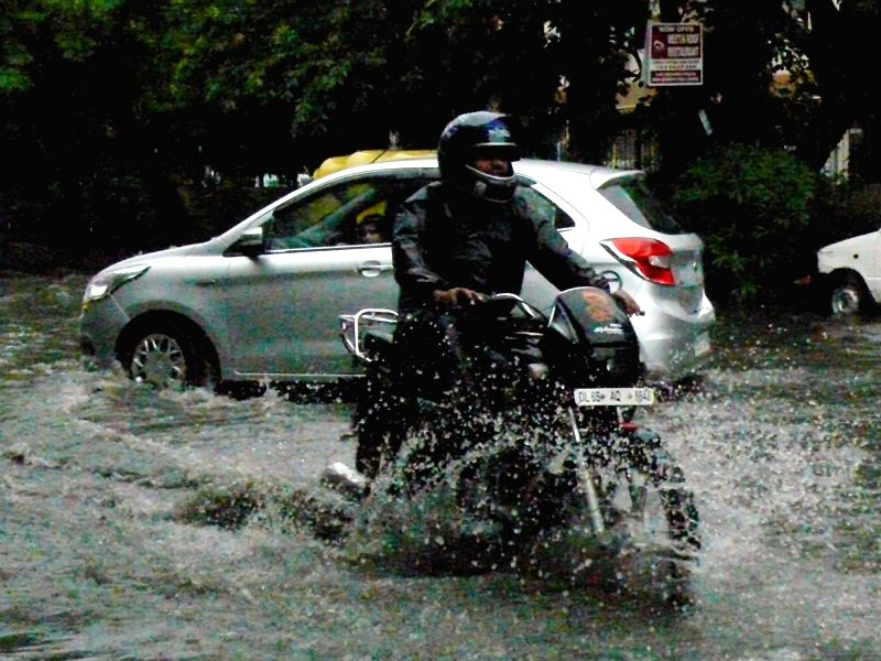 A motorcyclist wades through water logged street after a heavy downpour in New Delhi on July 26, 2018.