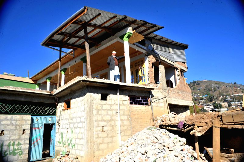 A Pakistani earthquake survivor stands at his damaged house in earthquake-hit northwest Pakistan's Lower Dir, Oct. 28, 2015. The international community continued ...