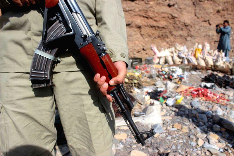 A Pakistani soldier stands guard beside seized explosives near northwest Pakistan's Peshawar on Nov. 18, 2015.