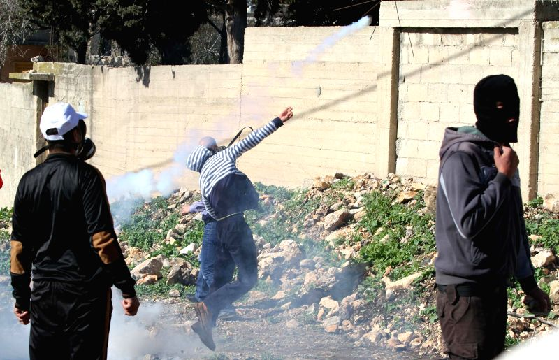 A Palestinian protester throws back a tear gas canister fired by Israeli soldiers during a protest against the expanding of Jewish settlements in Kufr Qadoom village ...